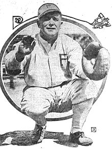 "A man in a white baseball uniform with a ""P"" on the chest and cap is crouched waiting to catch a ball in his catcher's mitt."