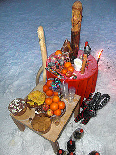 Two tables located in the snow. On the tables are various fruits and wooden quasi-anthropomorphic statues.