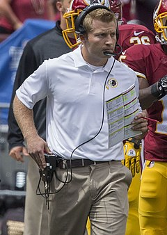 Photograph of McVay on a football sideline wearing a white Washington Redskins polo shirt, khaki pants and a headset and holding a football play sheet in his left hand