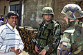 Sgt. Chuck Harman (center), 2nd Platoon, B Company, 11th Engineer Battalion, and Islam Zuzaku (right), an interpreter, speak to a Roma man during a patrol of the city of Gnjilane, Kosovo on May 27, 2001 010527-A-TH890-013.jpg