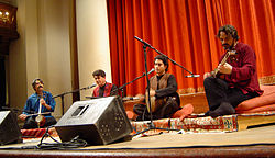 The four original ensemble members sit atop rugs and cushions onstage. The men all have their respective instruments, with microphones and monitor speakers before them. Behind them is a large, orange drapery.