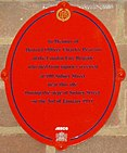 "Oval red plaque bearing the words ""In memory of District Officer Charles Pearson of the London Fire Brigade who died from injuries received at 100 Sidney Street near this site during the siege of Sidney Street on the 3rd of January 1911."""
