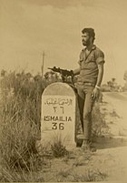 """A soldier with an Uzi next to a road sign reading """"ISMAILIA 36"""""""