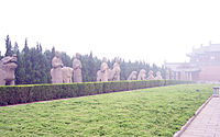 A number of stone statues, mostly of humans and lions, flanking a long paved road that leads to a large building obscured by fog or haze. The statues are separated from the road by a short hedge.