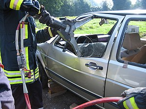 Hydraulic rescue tools - A hydraulic spreader in use, seen here widening a window on the door of a Volkswagen Golf Mk2 to allow fire crews access into the vehicle.