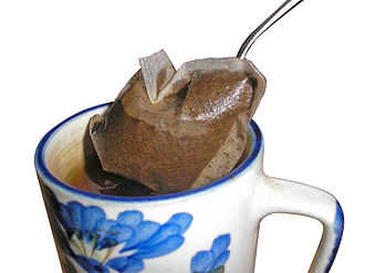 Tea bag - A tea bag being removed from a mug of hot tea to halt the brewing process