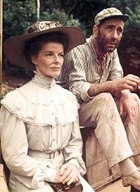 Hepburn is dressed in early-20th-century clothes, looking prim and proper. Behind her is Humphrey Bogart, also dressed as his character from The African Queen.