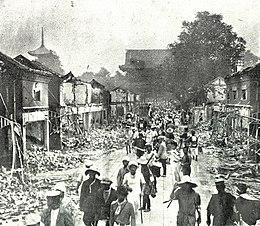Tiendas destruidas alineadas a lo largo de la calle hacia el templo Sensō-ji en Asakusa, con gente caminando, 1923. Tanto la puerta del medio (centro) como la pagoda (izquierda, perdida más adelante) están en la foto de pie.