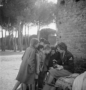 Curiosity - Curious children gather around photographer Toni Frissell, looking at her camera
