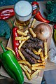 Top view of grilled Serbian sausages with vegetables, french fries and beer. (49151848768).jpg