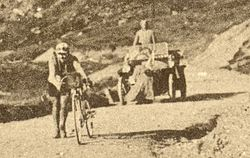 A man walking uphill, alongside his bicycle, followed by a car.