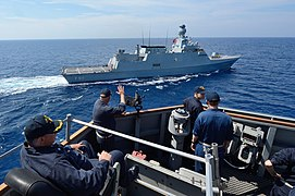 U.S. Navy Cmdr. Russell Caldwell waves to the Turkish corvette TCG Heybeliada (F 511) from aboard the guided missile destroyer USS Ross (DDG 71) in the Mediterranean Sea during a passing exercise Sept 140902-N-IY142-159.jpg