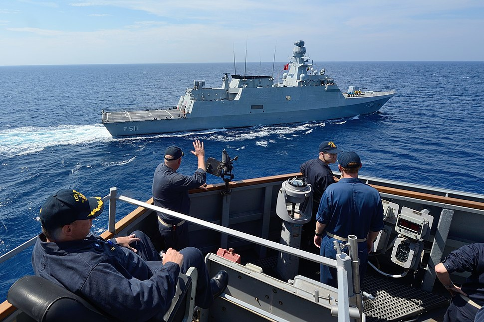 U.S. Navy Cmdr. Russell Caldwell waves to the Turkish corvette TCG Heybeliada (F 511) from aboard the guided missile destroyer USS Ross (DDG 71) in the Mediterranean Sea during a passing exercise Sept 140902-N-IY142-159
