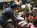 U.S. Navy Operations Specialist 2nd Class Alpana Trivedi, assigned to high speed vessel Swift (HSV-2), hands a stuffed animal to a child at the Espace Enfants orphanage in Pointe-Noire, Republic of Congo 120517-N-GA722-101.jpg