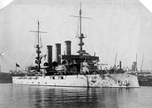 A white battleship with three smokestacks and two tall masts sitting in port.