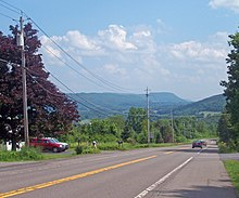 A two-lane road descending left to right across the bottom half of the image, with telephone poles along its left side, to a right turn. In the distance is a valley that extends to the rear of the field of view.