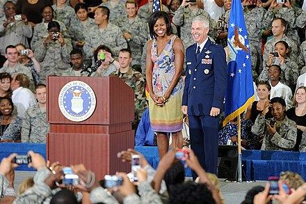 Obama and General Charles R. Davis smile to the crowd before speaking on her mission to help military families, October 2009. US Army 53373 First Lady Embarks on Mission to Help Military Families.jpg
