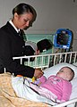 US Navy 070707-N-6710M-029 Seaman Francheska K. Montoya spends a few moments with a child at Sydney's Children's Hospital during a community relations project as part of a four-day port visit by dock landing ship.jpg