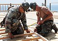 US Navy 080705-N-1424C-902 Construction Electrician 1st Class Samuel Roman and Builder 3rd Class Christopher Eyles, assigned to Amphibious Construction Battalion (ACB) 1 rebuild the deck of a platform overlooking Red Beach.jpg