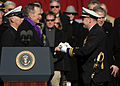 US Navy 090110-N-4408B-477 Lt. Cmdr. George Brickhouse, assigned to the aircraft carrier USS George H.W. Bush (CVN 77) accepts a long glass symbolizing the setting of the first watch from former President George H.W. Bush.jpg