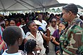 US Navy 090506-F-5647K-008 Master-at-Arms 1st Class Diedre Davis, embarked aboard the Military Sealift Command hospital ship USNS Comfort (T-AH 20), speaks with patients in line at the Multi Cultural Center.jpg