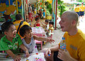 US Navy 100812-N-8539M-209 Crypotlogic Technician 3rd Class Manuel Dominguez practices basic English phrases with children at a Da Nang primary school.jpg