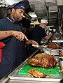 US Navy 111124-N-YC505-075 Culinary Specialist 2nd Class Charles Masten carves a turkey in a galley aboard the aircraft carrier USS George H.W. Bus.jpg