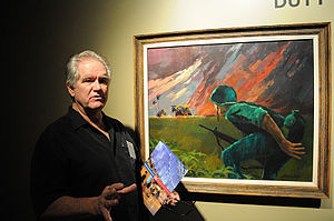 """Vietnam Combat Artists Program - Roger Blum, Vietnam Combat Artist Team I, discusses his painting """"Attack at Twilight,"""" completed with acrylic. The painting was inspired by Blum's first view of a burning """"hooch,"""" or hut, and he used dramatic lighting to emphasize the emotion of the painting."""