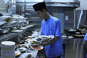 Nasi Padang - The waiter stacking plates of dishes in his hand prior to hidang serve in a Padang restaurant