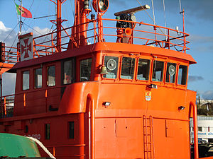 Bridge (nautical) - Bridge of the tugboat Leão dos Mares. An open compass platform, which still has the traditional binnacle, now also houses a radar antenna and sits above the enclosed wheel house. The circular devices in the windows are Kent screens.