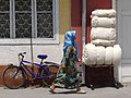 Woman Walks Past Bicycle and Cotton Bales - Margilon - Uzbekistan (7551670490).jpg
