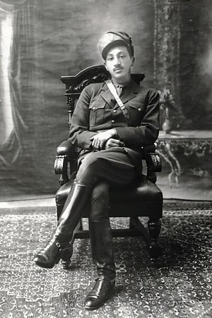 Mohammed Zahir Shah - Studio photograph of Zahir Shah in military uniform, seated in a heavy, carved armchair. (1930s)