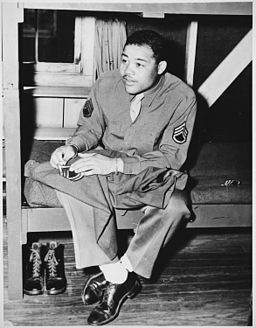 """World Heavyweight champ Joe Louis (Barrow) sews on the stripes of a technical sergeant-to which he has been promoted. - NARA - 535937"