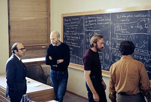 Kip Thorne - Discussion in the main lecture hall at the École de Physique des Houches (Les Houches Physics School), 1972. From left, Yuval Ne'eman, Bryce DeWitt, Thorne, Demetrios Christodoulou.