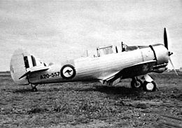 Piston-engined military monoplane parked on grass airfield