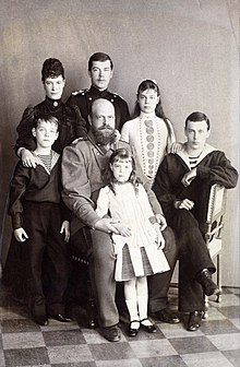 Black-and-white photograph of bald and bearded Alexander III wearing a military uniform and surrounded by his children and wife.