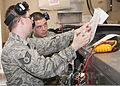 A U.S. Air Force staff sergeant, left, serving as an instructor, helps Senior Airman Joseph Szymanski, with the 361st Training Squadron, check an electrical wiring diagram to troubleshoot an electrical problem 110608-F-NS900-014.jpg