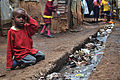 A young boy sits over an open sewer in the Kibera slum, Nairobi.jpg