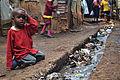 A young boy sits over an open sewer in the Kibera slum, Nairobi.jpg
