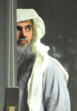 Abu Qatada and escort prior to take off (cropped).jpg