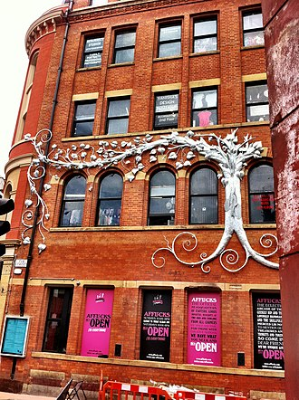 Afflecks - The Tib Street side of the building, June 2011. The artworks and mosaics have been removed and replaced with hoarding displaying details about the store. The silver tree was a new installation in 2011