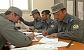 Afghan National Civil Order Police Afghan Gendarmerie Force trainers review the final evaluations of trainees' paperwork and certificates (4461526891).jpg