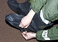 Airman Kevin Camara, 2nd Communications Squadron, prepares himself for Chemical Warfare Training, March 1, 2002, at Barksdale Air Force Base, La., by putting on his over garment and cover boots 020301-F-JG870-008.jpg