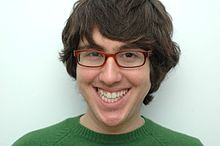 Amir Blumenfeld with long hair, red glasses and a green sweater, grinning before a white background