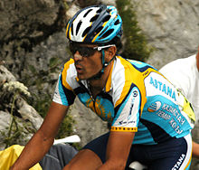 A cyclist in a blue and yellow jersey with white trim. His bicycle is not visible, but he is in riding position. He wears sunglasses, a helmet to match his jersey, and a bandage on his nose.