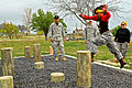 Ariel Ross leaps over an obstacle course.jpg