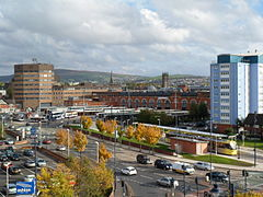 A Metrolink and bus station in front of office buildings. There are hills in the background and a road in the foreground