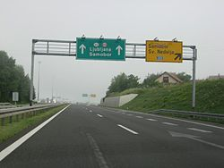 Directional traffic signs placed on a gantry ahead of a motorway exit