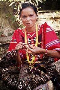 Woman in red decorated blouse making bracelets