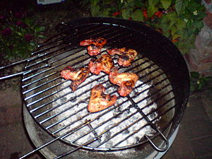 English: Chicken wings being cooked slowly ove...